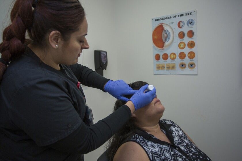 Silvia Fletes gives Rosa Guzman eyedrops before photographing her retinas to screen for diabetic retinopathy.