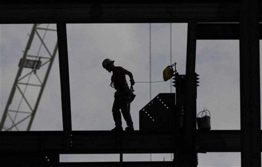 An ironworker walks across a beam on a building under construction at  Drexel University. One EconoMeter panel wonders starting if federal actions to start more construction would boost the economy.(AP Photo/Brynn Anderson)