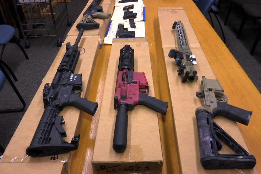"""""""Ghost guns"""" on display on boxes on a table."""