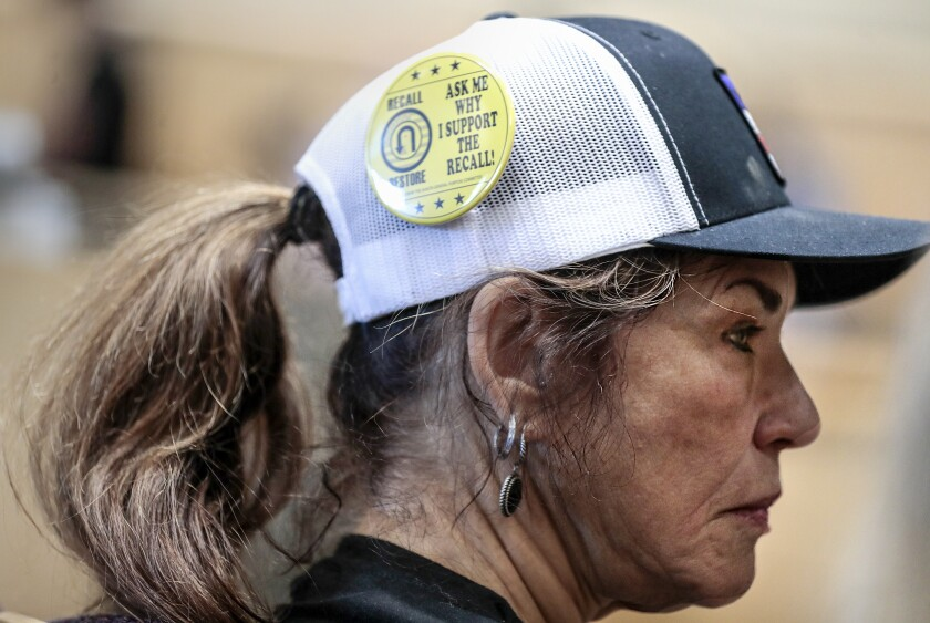 A yellow button on a woman's cap reads, Ask me why I support the recall!