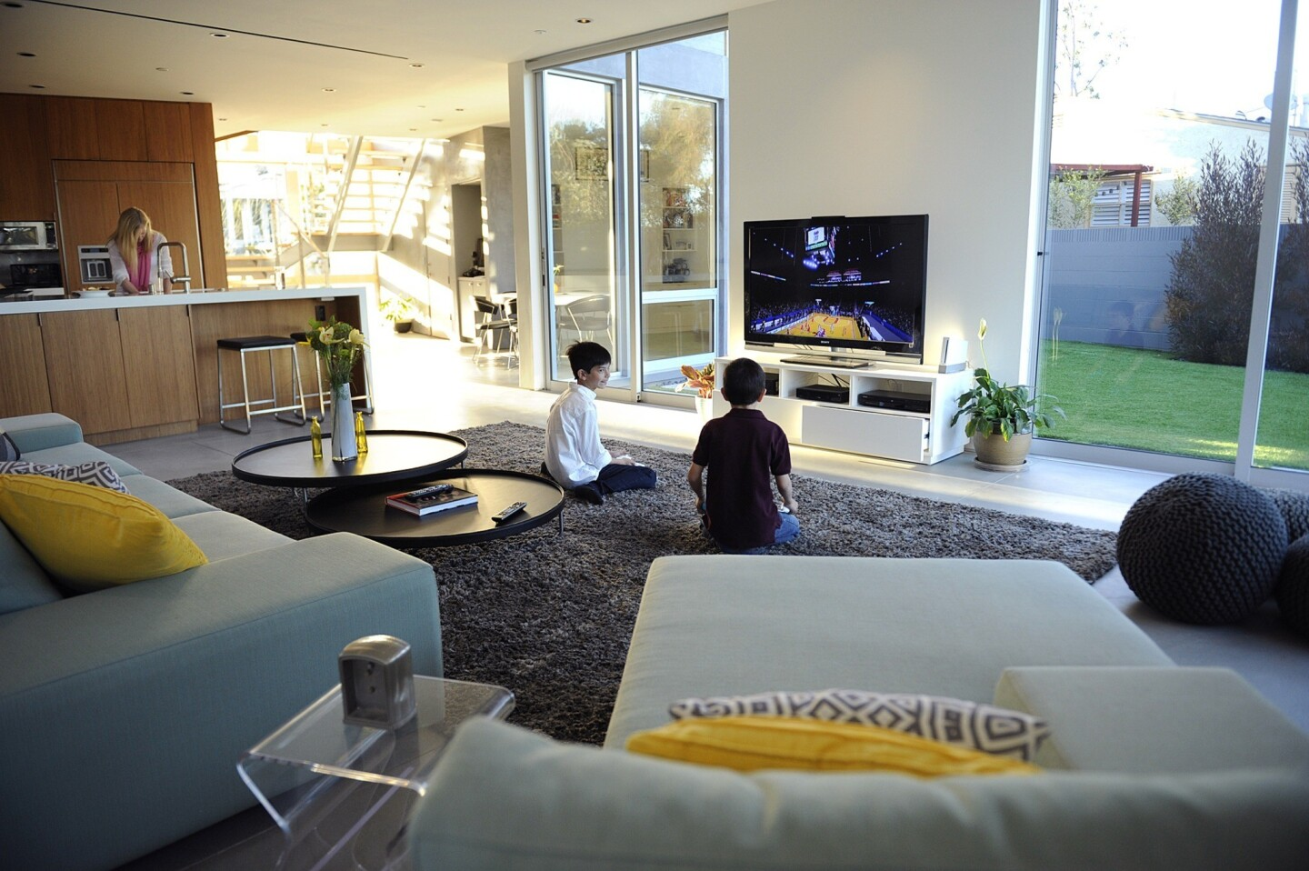 Tanner and Kyle Chen play a video game while their mom, Tiffany, makes dinner. The kitchen sink is the command and control center, with sightlines to wherever the kids are playing — family room or backyard.