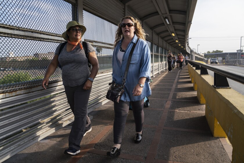 """Volunteer lawyers Lillian G. Gonzalez, left, and Jodi Goodwin walk to Matamoros to hold a workshop for asylum seekers who have been sent back to wait in Mexico for their asylum claim under the Trump administration's """"Remain in Mexico"""" policy."""