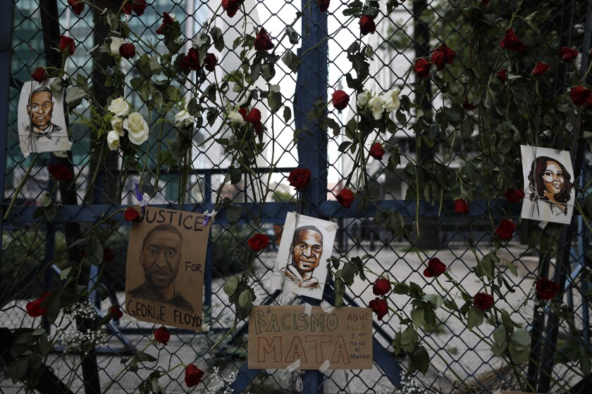 """Images of George Floyd, a handcuffed black man who died after being taken into police custody in Minneapolis, hang surrounded by roses on a security barrier outside the U.S. embassy in Mexico City, Saturday, May 30, 2020. A sign in Spanish reads: """"Racism kills, here, there, and in the whole world,"""" on the display put up by a group of Americans living in Mexico, along with other ex-pat and Mexican friends. (AP Photo/Rebecca Blackwell)"""