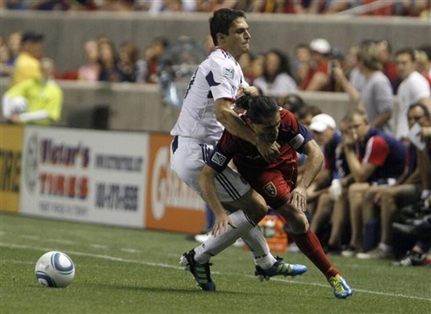 Chicago Fire defender Josip Mikulic, left, takes down Real Salt Lake forward Fabian Espindola during the first half of an MLS soccer match in Salt Lake City, Wednesday, Sept. 28, 2011. (AP Photo/Jim Urquhart)