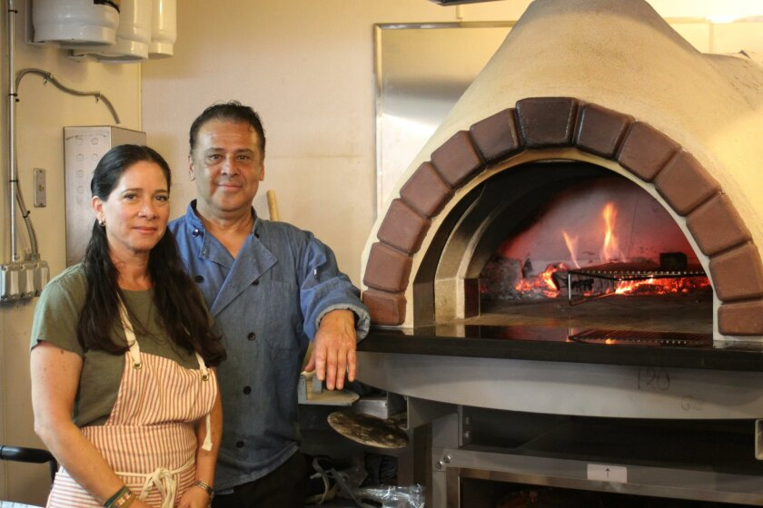 Co-owners Rosendo and Christina Lomeli with the wood-burning oven at Lena. (Not pictured: son Andre)