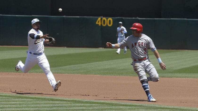 Oakland Athletics second baseman Franklin Barreto, left, throws to first base as Los Angeles Angels'