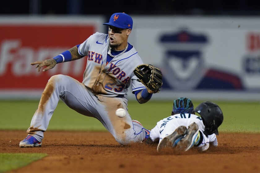 New York Mets second baseman Javier Baez (23) is unable to catch the throw as Miami Marlins' Jazz Chisholm Jr. steals second base during the sixth inning of a baseball game Thursday, Sept. 9, 2021, in Miami. (AP Photo/Wilfredo Lee)