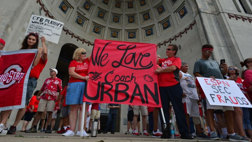 Supporters of Ohio State head football coach Urban Meyer hold signs at a rally at Ohio State University.