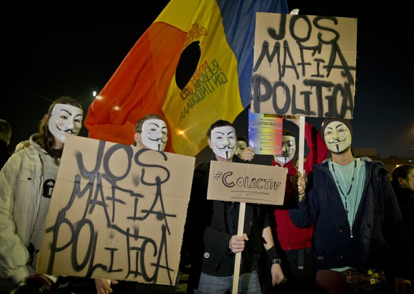 """Protesters wearing masks hold banners that read: """"Down the Political Mafia"""" during a rally calling for early elections, joined by thousands in University Square in Bucharest, Romania, Wednesday, Nov. 4, 2015. Prime Minister Victor Ponta announced the resignation of his government Wednesday followin"""