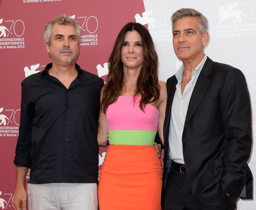 A la izq., el director mexicano Alfonso Cuarón, acompañado por los astros del cine Sandra Bullock y George Clooney.