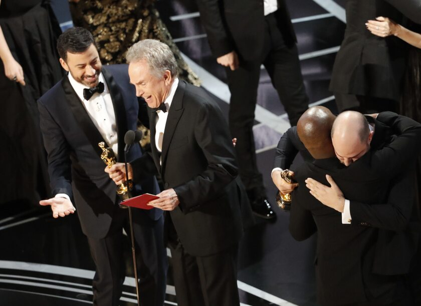"""Presenter Warren Beatty and host Jimmy Kimmel try to explain to the audience how the wrong envelope for best picture was read on stage during the Academy Awards telecast on Feb. 26. In background are """"Moonlight"""" writer/director Barry Jenkins, left and """"La La Land"""" producer Jordan Horowitz embracing."""