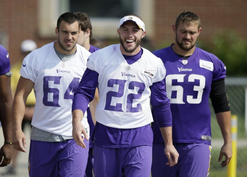 Minnesota Vikings free safety Harrison Smith (22) walks to the field with teammates before an NFL football training camp practice, Saturday, Aug. 2, 2014, in Mankato, Minn. (AP Photo/Charlie Neibergall)