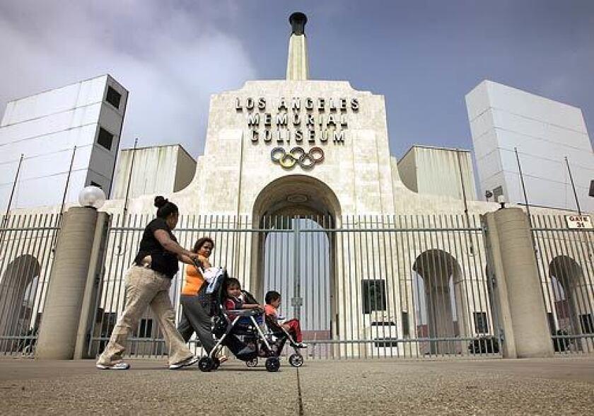 Maria Gonzales (left) walks her children with friend Victoria Guzman past the famous Los Angeles Coliseum in Exposition Park.