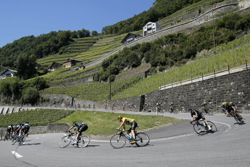 The pack with Britain's Chris Froome, wearing the overall leader's yellow jersey, passes through a hairpin turn during the seventeenth stage of the Tour de France cycling race over 184.5 kilometers (114.3 miles) with start in Bern and finish in Finhaut-Emosson, Switzerland, Wednesday, July 20, 2016. (AP Photo/Christophe Ena)