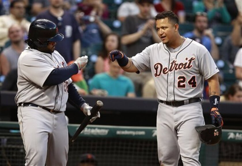 Detroit Tigers' Miguel Cabrera (24) is congratulated by Prince Fielder after Cabrera hit a home run during the sixth inning of a baseball game against the Houston Astros, Saturday, May 4, 2013, in Houston. (AP Photo/Patric Schneider)