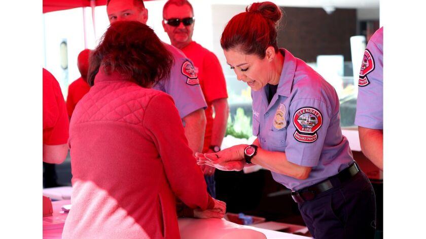 Glendale Fire Dept. ambulance operator Celine Gonzalez shows Manuela Fernandez how to properly perfo