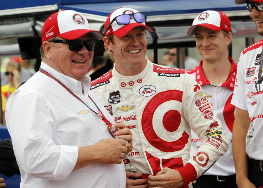 Scott Dixon, center, of New Zealand, laughs with car owner Chip Ganassi, left, after qualifying on the pole for the Indianapolis 500 auto race at Indianapolis Motor Speedway in Indianapolis, Sunday, May 17, 2015. (AP Photo/AJ Mast)