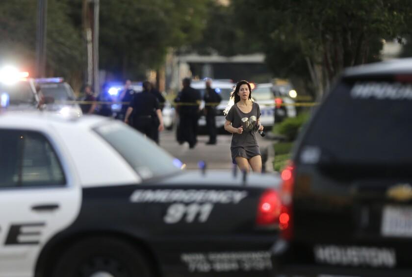 Jennifer Molleda corre por la calle Wesleyan Street para encontrase con su esposo Alan Wakim, quien se salvó de recibir dos disparos en el rostro cuando iba conduciendo su camioneta por la calle Law Street, en Houston, Texas, el lunes 26 de septiembre de 2016. Nueve personas resultaron heridas de bala, una de ellas de gravedad, por un abogado que comenzó a disparar a la gente. La policía mató a agresor. (Mark Mulligan/Houston Chronicle via AP)