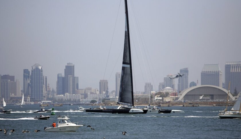 Along with an escort, BMW Oracle Racing's trimaran sails across San Diego Bay. It will go against Alinghi in February's best-of-three America's Cup.