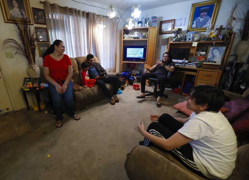 Maria Peñuelas, 45, sits in their living room with her four boys on April 30.