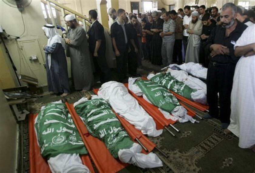 FILE- In this Aug. 15, 2009 file photo, Palestinian mourners pray next to the bodies of Hamas security forces, killed during a bloody battle in Rafah, southern Gaza Strip with fighters espousing an even more militant brand of Islam. The rivalry between Gaza's Hamas rulers and small, shadowy armed groups calling themselves Jihadi Salafis is adding a new and potentially ominous ingredient to the Palestinian-Israeli conflict. (AP Photo/Eyad Baba, File)