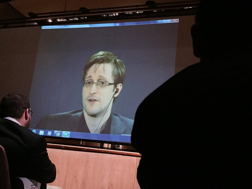 Former National Security Agency contractor Edward Snowden, center speaks via video conference to people in the Johns Hopkins University auditorium, Wednesday, Feb. 17, 2016, in Baltimore. Hopkins students spent months arranging the live video conference Wednesday night with Snowden, according to th