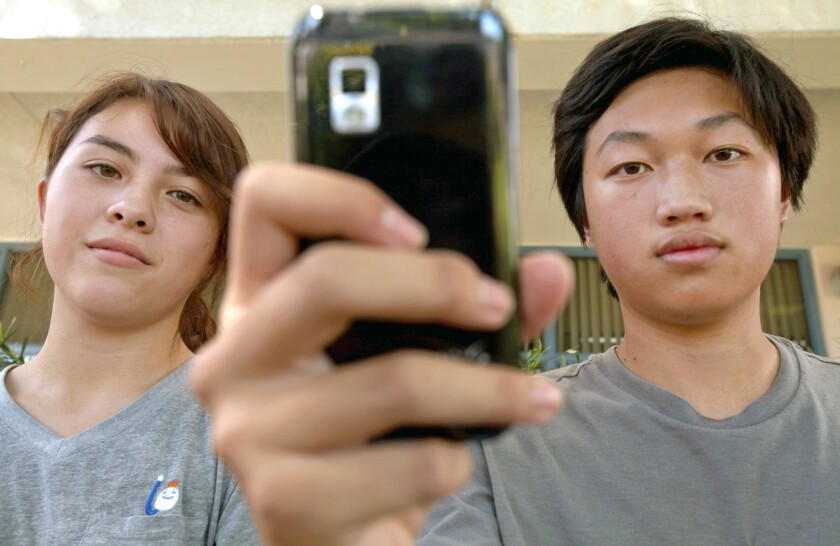 Young Cho, left, 16, of Glendale, and Christopher Chung, right, 16, also of Glendale, stand in front of their school, Herbert Hoover High School, in this September 2013 file photo.