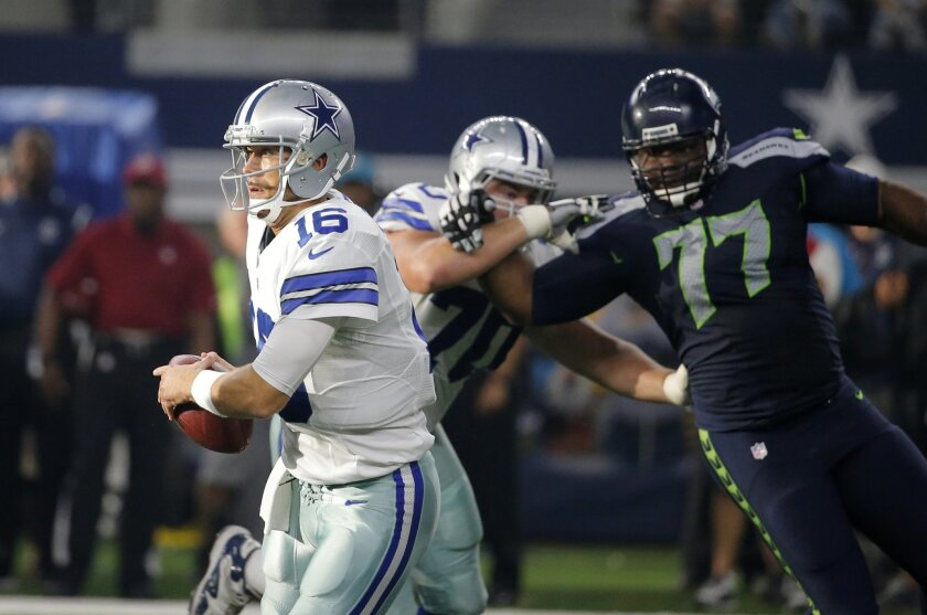 Dallas Cowboys' Matt Cassel (16) runs out of the pocket under pressure from Seattle Seahawks' Ahtyba Rubin (77) in the first half of an NFL football game Sunday, Nov. 1, 2015, in Arlington, Texas. (AP Photo/Brandon Wade)