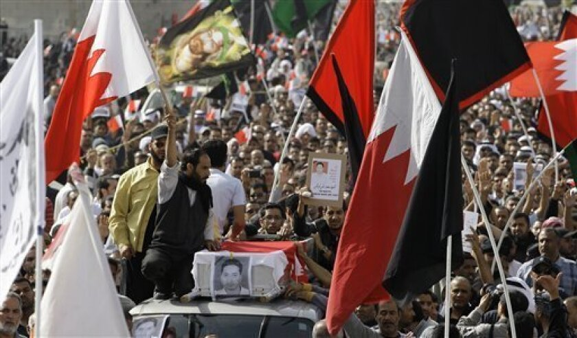 A funeral procession for Mahmoud Maki Abu Taki, 22, who died during clashes between Bahraini anti- government and riot police early Thursday, moves slowly through the streets in Sitra village, Bahrain, Friday, Feb. 18, 2011. (AP Photo/Hassan Ammar)