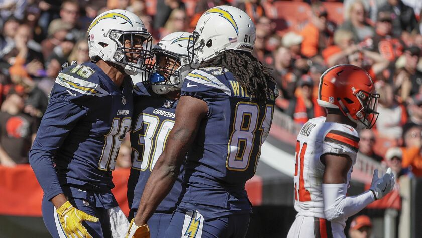 Tyrell Williams celebrates with teammates Austin Ekeler and Mike Williams after catching a 29-yard touchdown pass from Chargers quarterback Philip Rivers.
