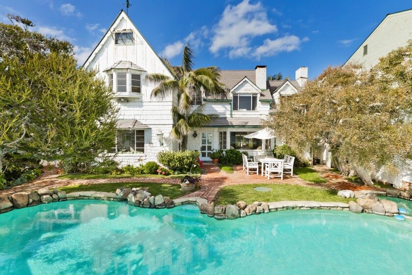 The Cape Cod-inspired compound sits behind fences and gates on an oceanfront lot of about a third of an acre.