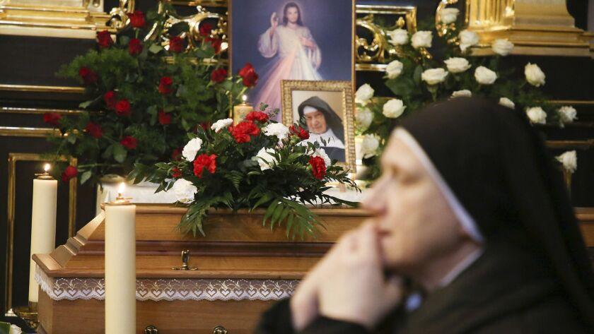 A nun prays beside the casket and photo of 110-year-old Roman Catholic Sister Cecylia Roszak, believ