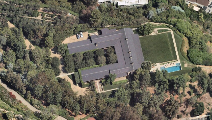 An aerial view of the 26,619-square-foot, U-shaped home surrounded by trees, a lawn and a swimming pool
