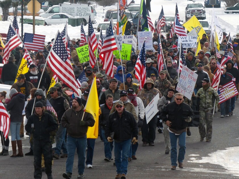 Protesters march on Court Avenue in Burns, Ore., in support of members of a ranching family facing jail time for arson.