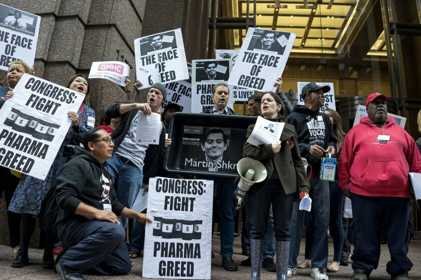 FILE - In this Oct. 1, 2015, file photo, activists hold signs containing the image of Turing Pharmaceuticals CEO Martin Shkreli in front the building that houses Turing's offices, during a protest in New York highlighting pharmaceutical drug pricing. Americans from across the political spectrum are worried about the cost of prescription drugs for serious diseases.