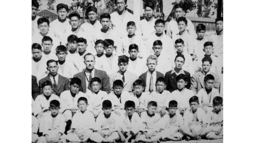 The close-up shows a row of men in the third row wearing suits, L-R: Seigoro Murakami, Jack Sergel,