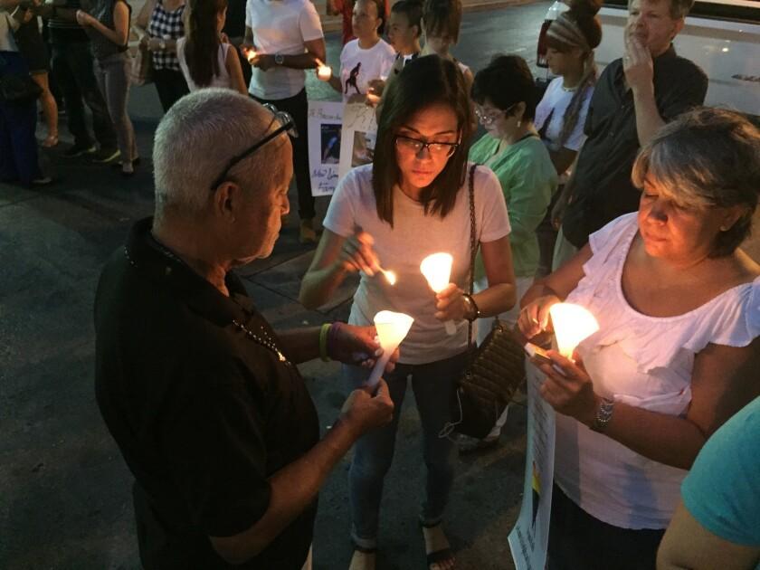 Gente enciende velas en Ponce, Puerto Rico, durante una vigilia por las víctimas de una masacre en un club nocturno gay de Orlando, Florida. Al menos cinco de las 49 víctimas eran de Ponce, la segunda ciudad de Puerto Rico. (AP Foto/Danica Coto)