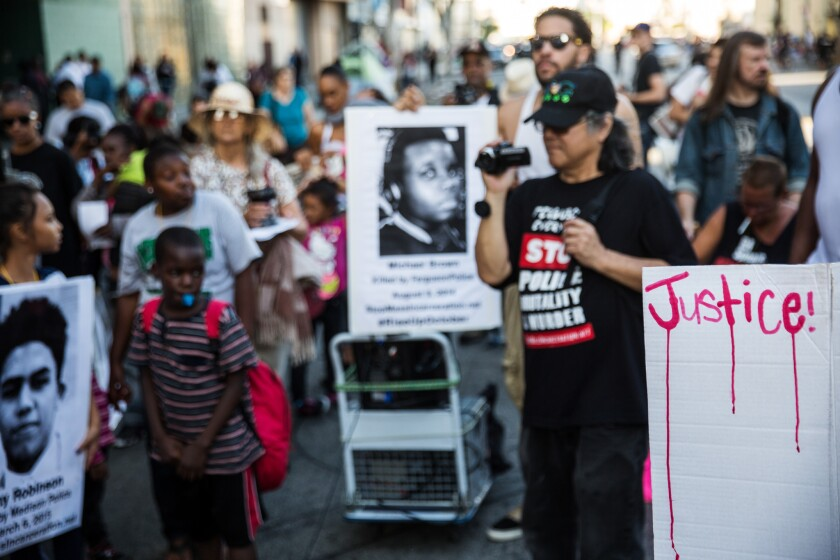 """Protesters against police violence stop at the site where Charly """"Africa"""" Keunang was killed on skid row in 2015."""