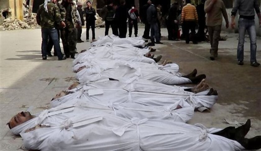 FILE - This file citizen journalism image taken on, Sunday, March. 10, 2013 and provided by Aleppo Media Center AMC which has been authenticated based on its contents and other AP reporting, shows Syrians standing next to dead bodies that have been pulled from the river near Aleppo's Bustan al-Qasr