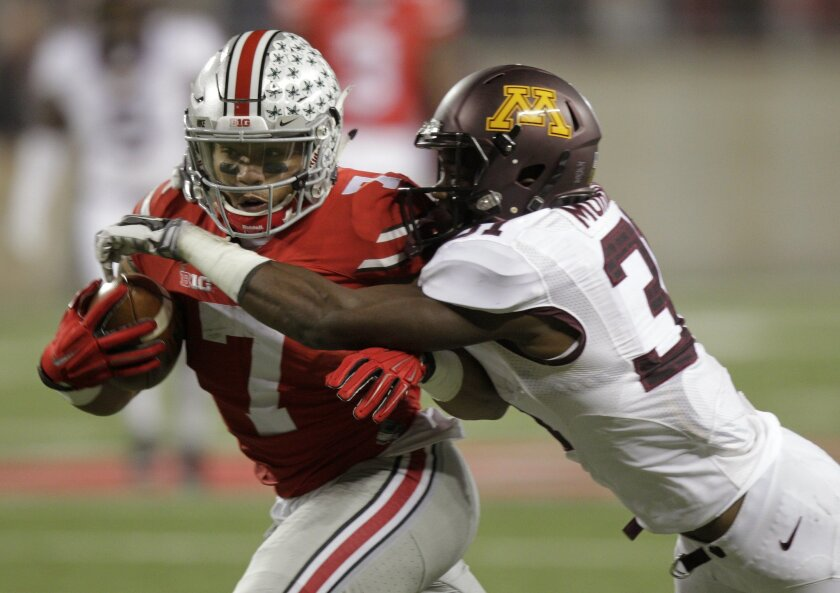Ohio State running back Jalin Marshall, left, runs the ball after a catch as Minnesota defensive back Eric Murray makes the tackle during the second quarter of an NCAA college football game Saturday, Nov. 7, 2015, in Columbus, Ohio. (AP Photo/Jay LaPrete)