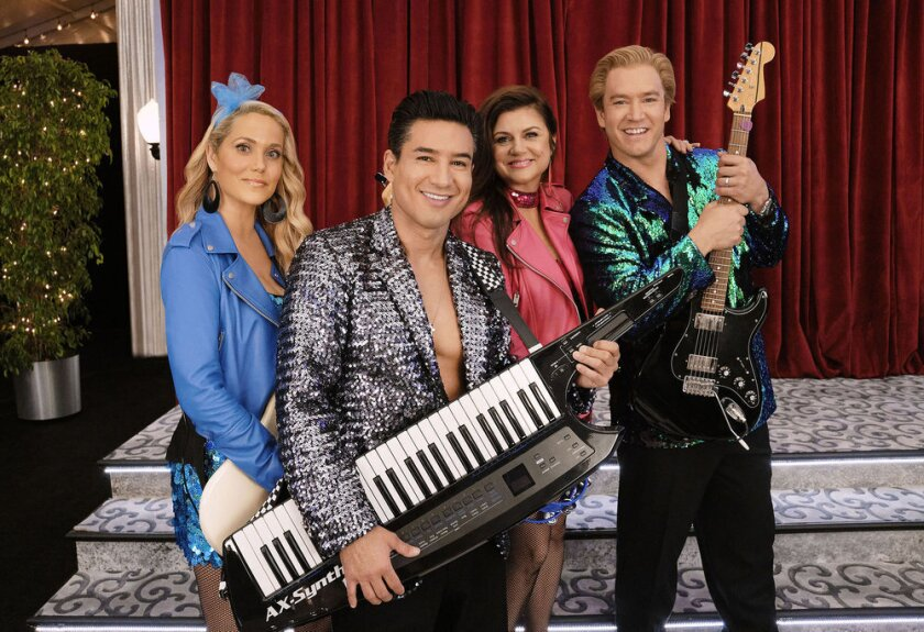 """This image released by Peacock shows Elizabeth Berkley as Jessica Spano, Mario Lopez as A.C. Slater, Tiffani Thiessen as Kelly Kapowski, and Mark-Paul Gosselaar as Zack Morris who appear in the reboot of """"Saved By the Bell."""" Zack Morris is now the California governor who has a son at Bayside High, Jess is a guidance counselor and A.C. Slater is now the gym teacher at Bayside. (Trae Patton/Peacock via AP)"""
