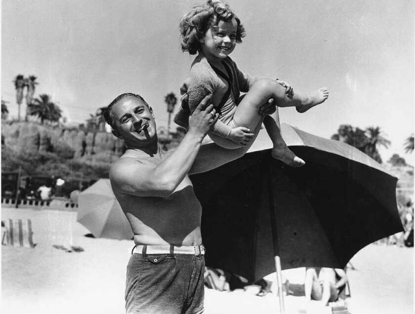 Shirley Temple, who died Monday at 85, has fun with her father George in this photo from 1935.