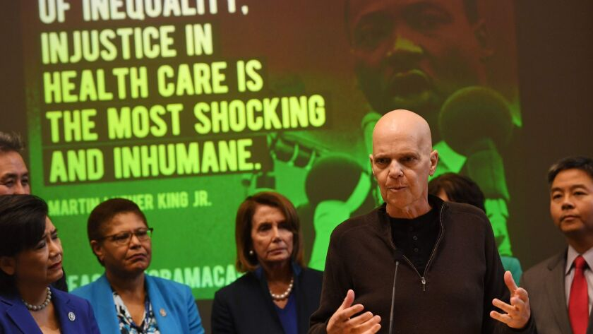 Cancer patient Doug Lunn, who says Obamacare saved his life, speaks beside Nancy Pelosi and House Democrats at an event to protect the Affordable Care Act in downtown L.A. on Jan. 16.
