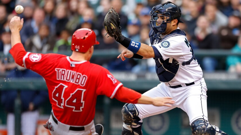 Former Mariners catch Jesus Montero takes a throw at the plate before tagging out the Angels' Mark Trumbo during a game in 2014.