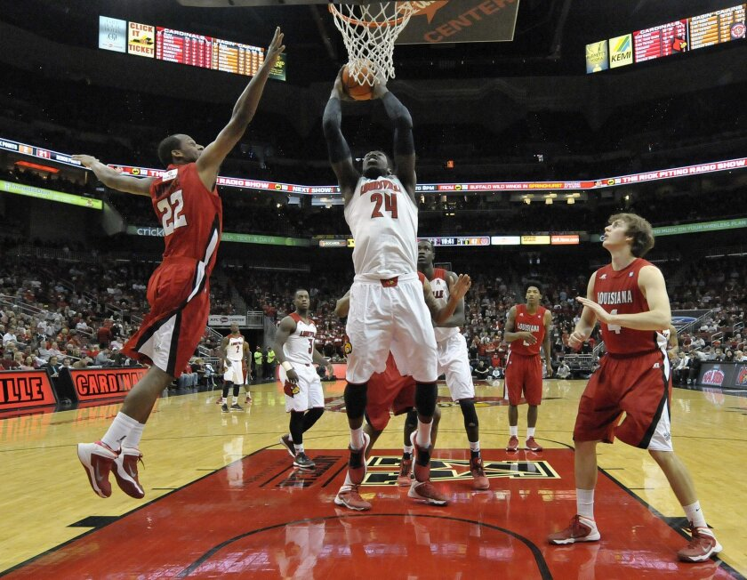 Louisville's Montrezl Harrell, center, goes up for a shot between the defense of Louisiana Lafayette's Elfrid Payton, left, and Steven Wronkoski during the second half of an NCAA college basketball game Saturday Dec. 7, 2013, in Louisville, Ky. Louisville defeated Louisiana Lafayette 113-74. (AP Photo/Timothy D. Easley)