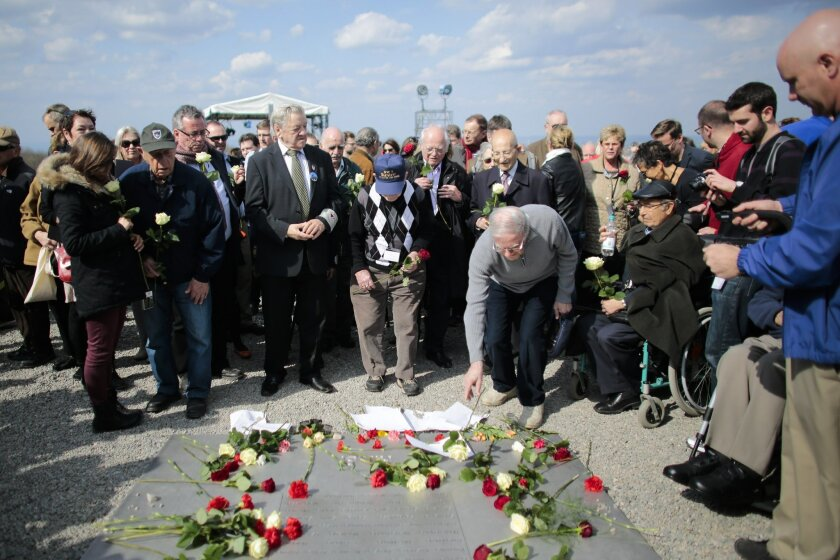 Buchenwald survivor Henry Oster, center right, and veteran United States medic James E. Anderson, center, who was with the US liberation troops, lay down flowers with other veterans prior to a minute of silence at 15:15 in the afternoon to mark the 70th anniversary of the liberation of the former N