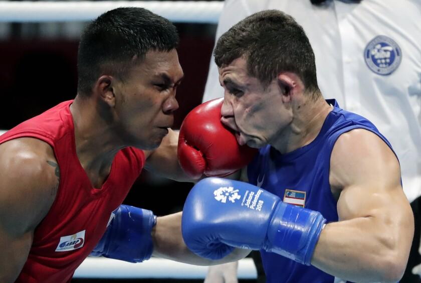 El filipino Eumir Félix Marcial (izq) se faja con el uzbeco Israil Madrimov en los Juegos Asiáticos