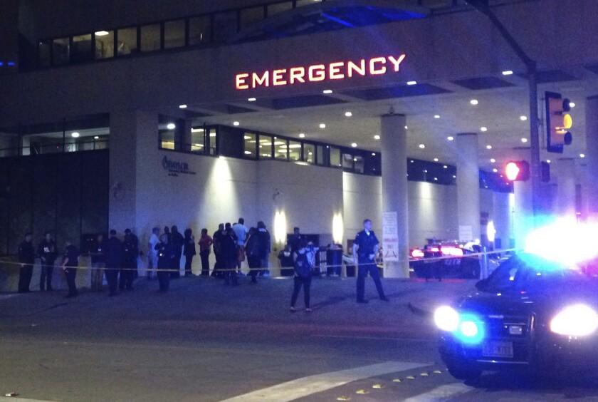 Policías y otras personas congregadas a la entrada de la unidad de urgencias del centro médico Baylor en Dallas, donde varios agentes fueron ingresados tras un tiroteo el jueves 7 de julio de 2016.. (AP Foto/Emily Schmall)