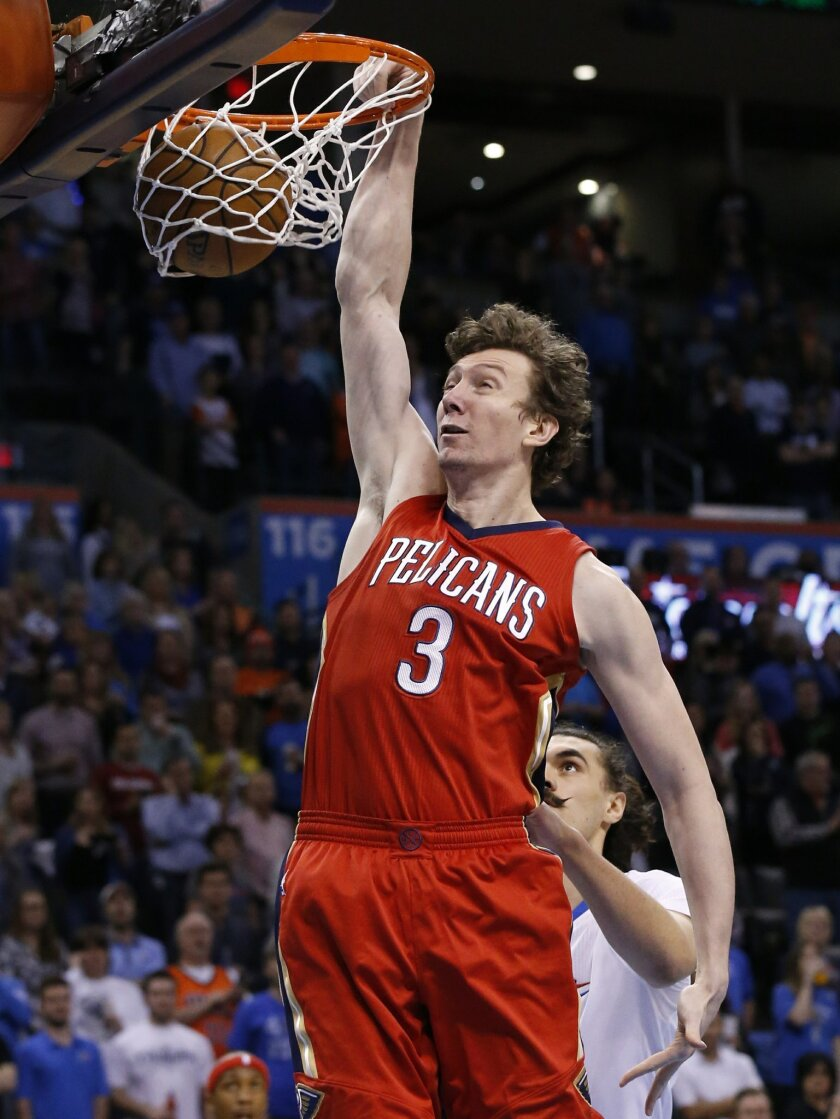 New Orleans Pelicans center Omer Asik (3) dunks in front of Oklahoma City Thunder center Steven Adams, right, in the first quarter of an NBA basketball game in Oklahoma City, Thursday, Feb. 11, 2016. (AP Photo/Sue Ogrocki)