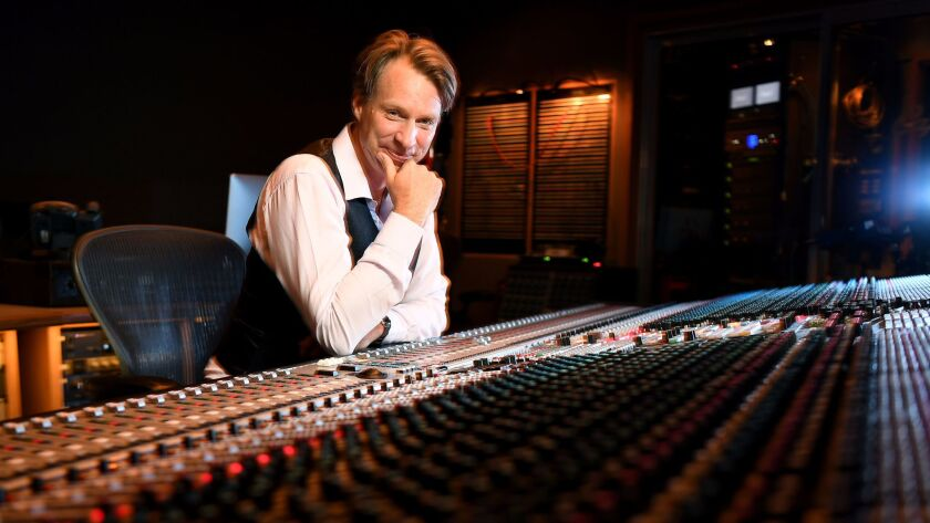 Producer Giles Martin (son of original Beatles producer George Martin) sits at the mixing console at